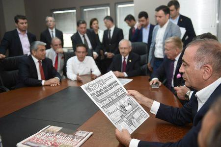 Gursel Tekin, a lawmaker from the main opposition Republican People's Party (CHP) holds a print copy of Sozcu daily newspaper as they visit the publication's headquarters in Istanbul