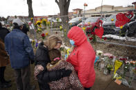 Mourners embrace after leaving bouquets on a fence put up around the parking lot where a mass shooting took place in a King Soopers grocery store Tuesday, March 23, 2021, in Boulder, Colo. (AP Photo/David Zalubowski)