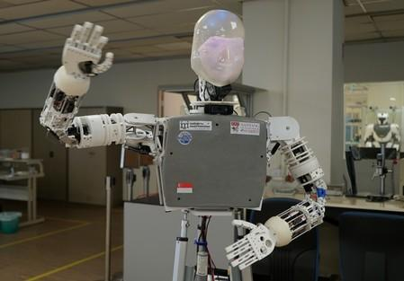 A robot named EDGAR, short for Expressions Display and Gesturing Avatar Robot, waves at the camera at a laboratory in Singapore