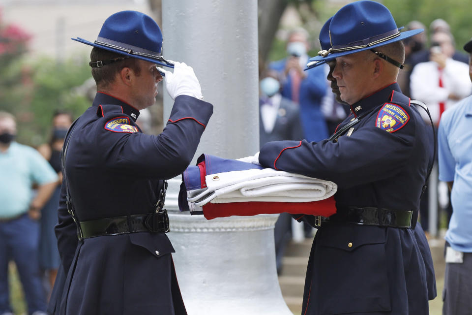 A Mississippi Highway Safety Patrol honor guard salutes the former Mississippi state flag after it was retired after being raised over the Capitol grounds one final time in Jackson, Miss., Wednesday, July 1, 2020. The banner was the last state flag with the Confederate battle emblem on it. (AP Photo/Rogelio V. Solis)