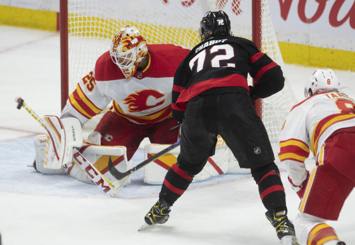 Ottawa Senators defenseman Thomas Chabot fires the puck wide past Calgary Flames goaltender Jacob Markstrom during the third period on an NHL hockey game, Wednesday, March 24, 2021 in Ottawa, Ontario. (Adrian Wyld/The Canadian Press via AP)