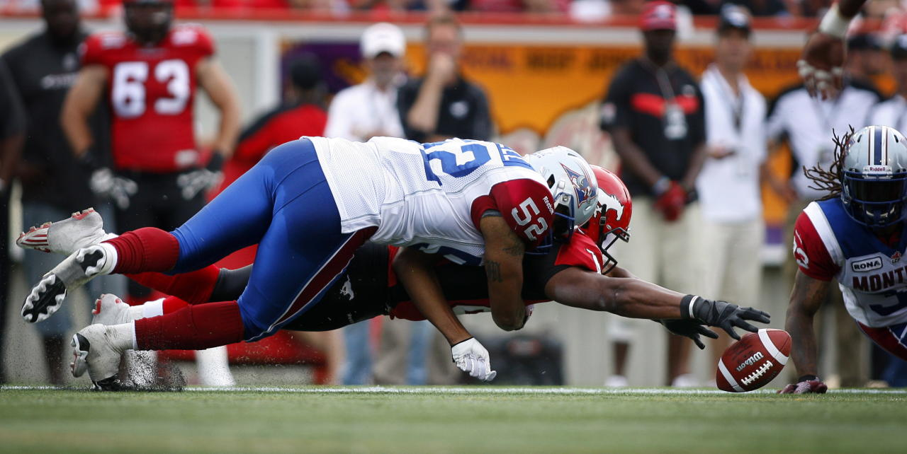 Montreal Alouettes' Marques Murrell, top, tackles Calgary Stampeders' Nik Lewis as he dives for a fumbled ball during fourth quarter CFL football action in Calgary, Alta., Sunday, July 1, 2012. THE CANADIAN PRESS/Jeff McIntosh