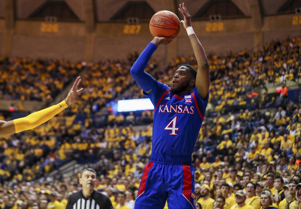 Feb 12, 2020; Morgantown, West Virginia, USA; Kansas Jayhawks guard Isaiah Moss (4) shoots a three pointer during the first half against the West Virginia Mountaineers at WVU Coliseum. Mandatory Credit: