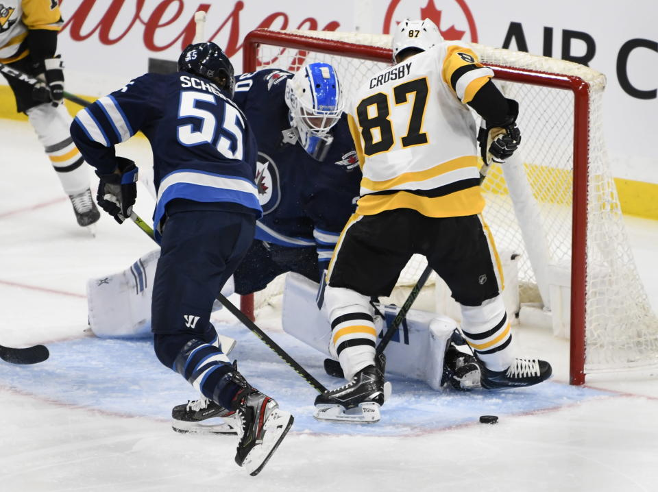 Winnipeg Jets goaltender Laurent Brossoit (30) makes a save on Pittsburgh Penguins' Sidney Crosby (87) during the third period of an NHL hockey game, Sunday, Oct. 13, 2019, in Winnipeg, Manitoba. (Fred Greenslade/The Canadian Press via AP)