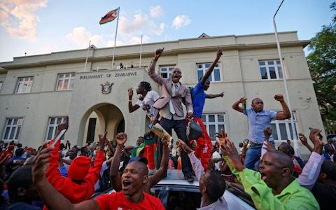 Zimbabweans celebrate outside the parliament building immediately after hearing the news that President Robert Mugabe had resigned - Credit:  Ben Curtis/ AP