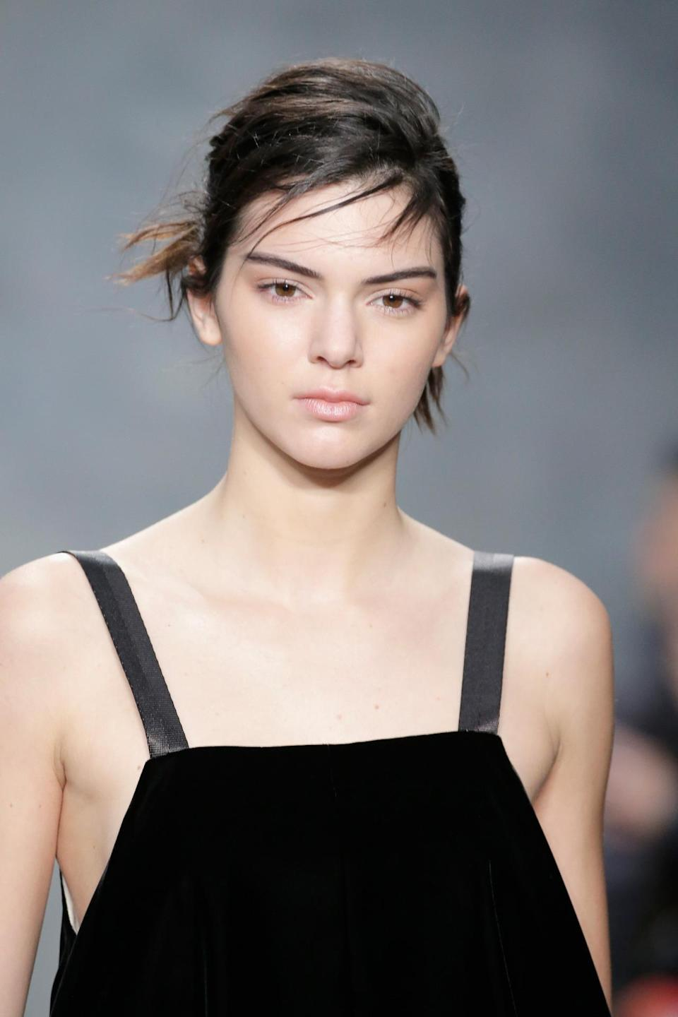 <p>What contouring? Walking the runway at Vera Wang Fall 2015, Jenner is barefaced with bold eyebrows and a messy updo. <i>(Photo: Getty Images)</i></p>