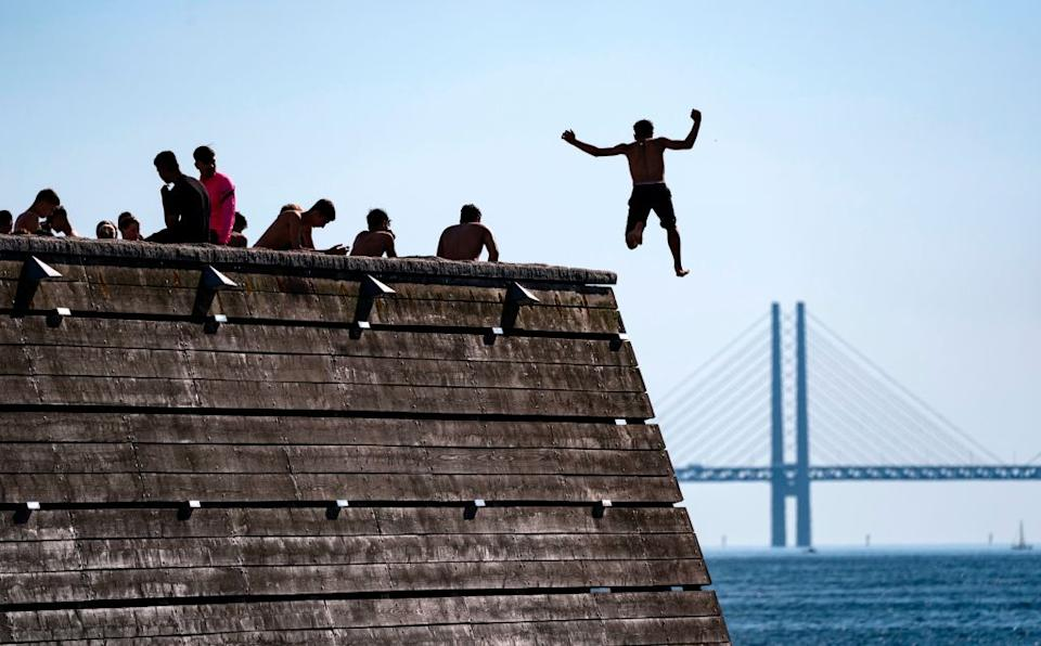 Swimmers brave the water in the shadow of the Oresund Bridge - getty