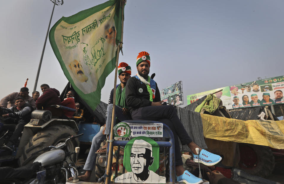 Indian farmers sit on their tractors after arriving at the Delhi-Uttar Pradesh border for Tuesday's tractor rally in New Delhi, India, Monday, Jan. 25, 2021. Thousands of farmers gathered on the borders of Delhi for a massive tractor rally on Tuesday against the three contentious farm laws when India will celebrate its Republic day with a military and cultural parade. The two-month-old old blockade of highways connecting the capital with the country's north continues as the talks have remained deadlocked with the government refusing to scrap the new agricultural reform laws which the farmers say will benefit large corporations. (AP Photo/Manish Swarup)