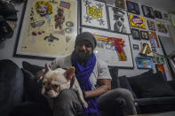 "Painter Guy Stanley Philoche, a 43-year-old Haitian immigrant and star in the New York art world, sits with his dog Picasso at their East Harlem home next to a wall of art collected from other artist, Thursday Nov. 19, 2020, in New York. After a hugely successful gallery show, Philoche wanted to treat himself to a fancy $15,000 watch, instead he bought the works of fellow artists struggling in the pandemic. ""I'm not a rich man,"" he said, ""but I owe a big debt to the art world."" (AP Photo/Bebeto Matthews)"