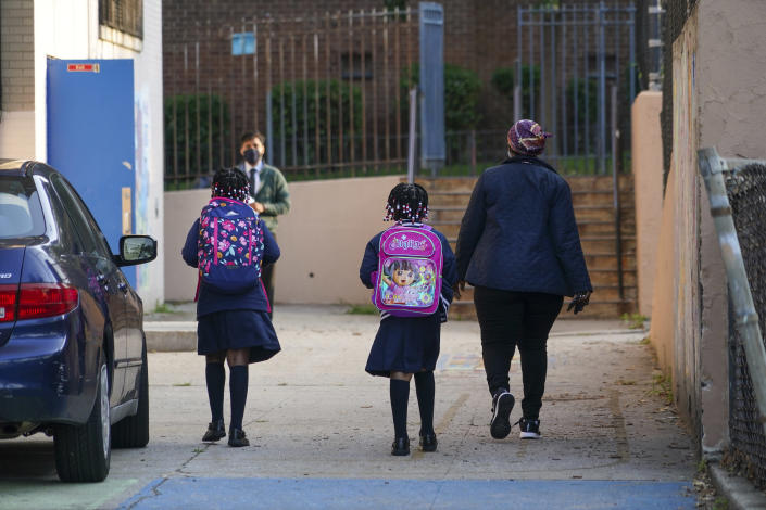 A parent drops her daughters off at a public school in New York, Sept. 21, 2020. (Chang W. Lee/The New York Times)