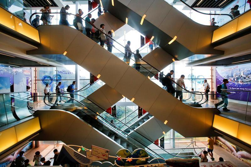 FILE PHOTO: Tourists descend on an escalator inside a shopping mall at the Peak in Hong Kong