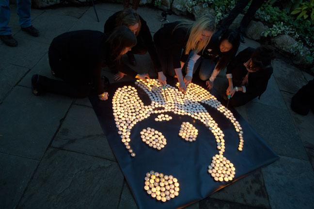 Lighting soya candles to create a candlelit WWF panda logo for Earth Hour 2011at Allan Gardens, Toronto, Ontario, Canada.