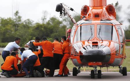 Indonesian Search and Rescue crews unload one of two bodies of AirAsia passengers recovered from the sea at the airport in Pangkalan Bun, central Kalimantan December 31, 2014. REUTERS/Darren Whiteside