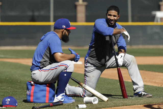 Texas Rangers' Rougned Odor, left, and Elvis Andrus talk while waiting to bat during spring training baseball practice Monday, Feb. 17, 2020, in Surprise, Ariz. (AP Photo/Charlie Riedel)