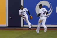 Miami Marlins right fielders Bryan De La Cruz and Jesus Sanchez (76) miss the ball hit by Washington Nationals' Lane Thomas during the eighth inning of a baseball game, Wednesday, Sept. 22, 2021, in Miami. (AP Photo/Marta Lavandier)