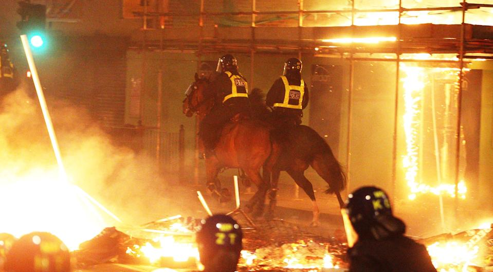 File photo of mounted police on the streets in Tottenham, north London as fire burns around them during riots. (Lewis Whyld/PA) (PA Archive)