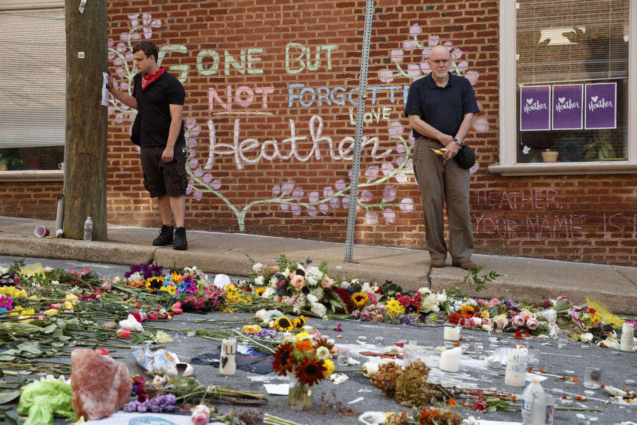 Jason Charter, left, of Washington, stands at a memorial, Wednesday, Aug. 16, 2017, in Charlottesville, Va., at the site where Heather Heyer was killed during a white nationalist rally. Charter was at the scene when a car rammed into a crowd of people protesting the rally. (AP Photo/Evan Vucci)