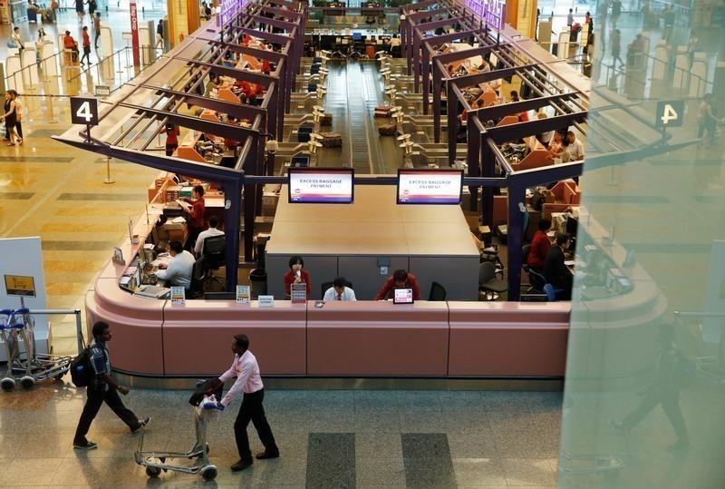 Passengers pass check-in counters at Singapore's Changi Airport Terminal One in Singapore