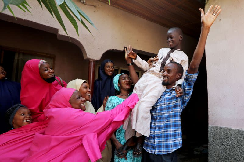 FILE PHOTO: Muhammed Bello, a rescued student, is carried by his father as his relatives celebrate after he retuned home in Kankara