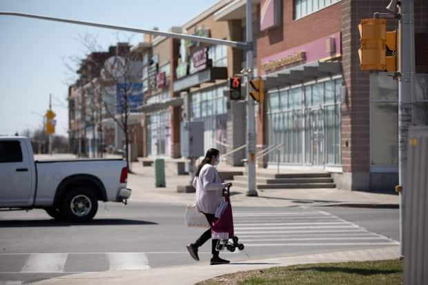 A pedestrian wearing a mask crosses Baseline Road near a cluster of businesses in early April 2021. On Sunday, the city's public health officials reported 370 new cases of COVID-19, the highest one-day total of the pandemic.  (Brian Morris/CBC - image credit)