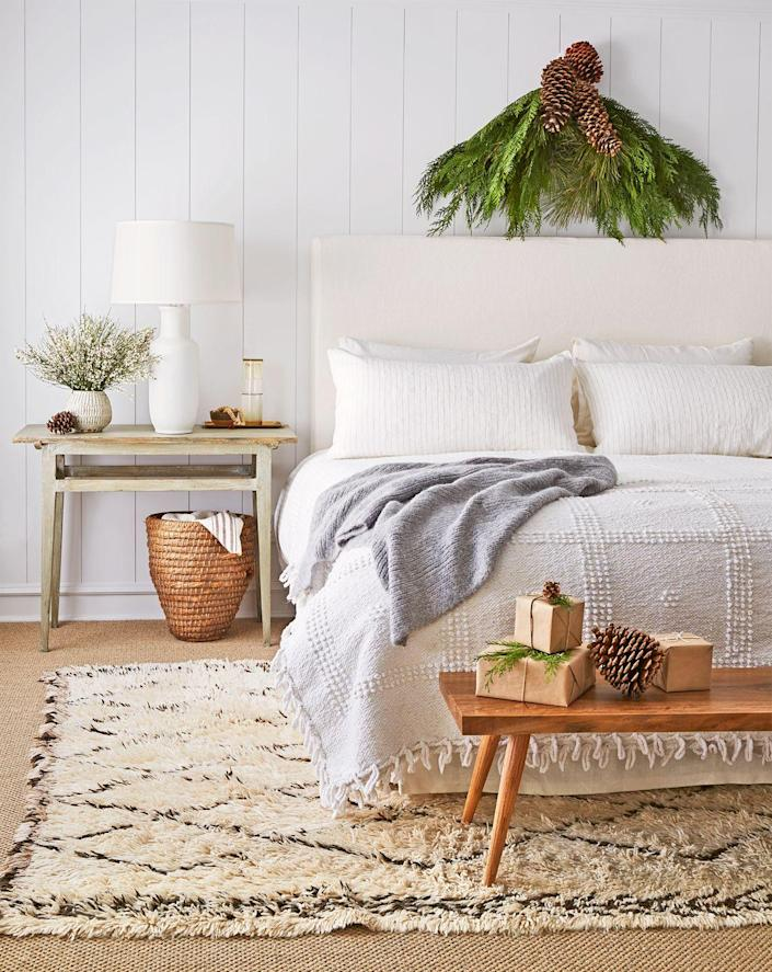 <p>If wreaths aren't your style, drape swag on the wall above your headboard. Keep it together with pinecones for an extra dose of holiday cheer. </p>