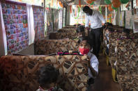 Children attend a mobile classroom set up in a parked bus by a social activist for children living in a slum in Mumbai, India Sunday, Aug. 15, 2021. (AP Photo/Rafiq Maqbool)