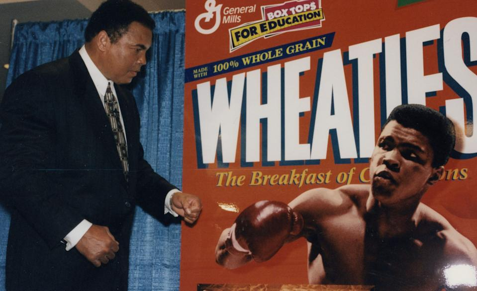 Muhammed Ali mirrors the boxing stance featured on the cover of the iconic 1999 Wheaties box on stage during a press conference at Madison Square Garden (credit: General Mills archives)