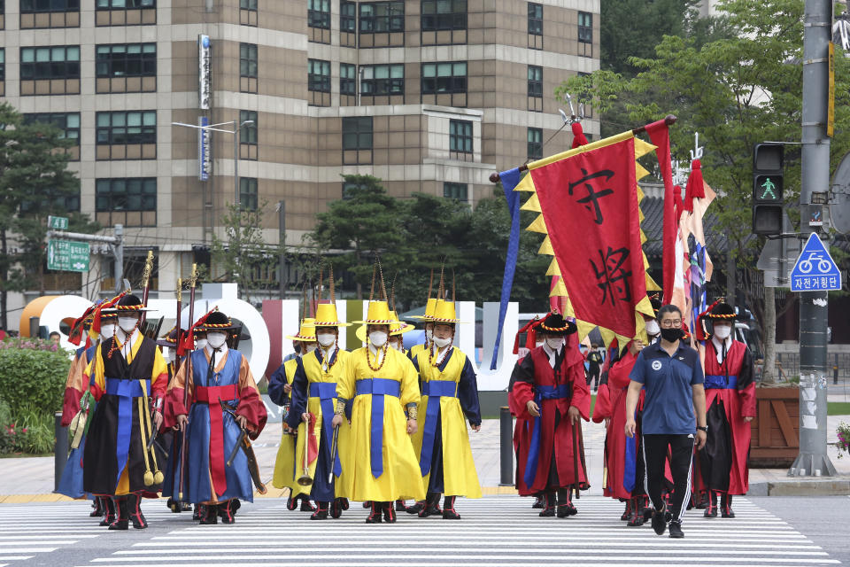 South Korean Imperial guards wearing face masks to help protect against the spread of the coronavirus cross a road in Seoul, South Korea, Wednesday, Aug. 5, 2020. (AP Photo/Ahn Young-joon)