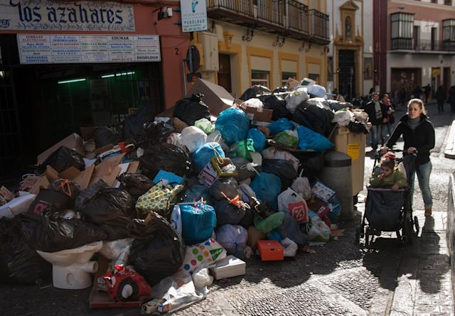 SEVILLE, SPAIN - FEBRUARY 06: A mother and child pass uncollected garbage during the 10th day of the Seville waste disposal strike on February 6, 2013 in Seville, Spain. Workers are striking over demands they take a 5% pay cut and extent their working week to 37.5 hours. (Photo by Denis Doyle/Getty Images)