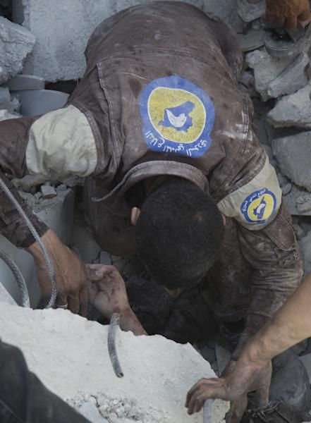 Syrian volunteers, known as the White Helmets, dig out a young boy trapped under the rubble of destroyed buildings following reported air strikes on the rebel-held neighbourhood of Al-Mashhad in Aleppo, on July 25, 2016 (AFP Photo/Karam Al-Masri)