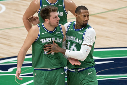 Dallas Mavericks guard Luka Doncic (77) is held back by forward James Johnson (16) as he argues with referees after being called for a technical foul during the first half of an NBA basketball game against the Orlando Magic, Saturday, Jan. 9, 2021, in Dallas. (AP Photo/Jeffrey McWhorter)
