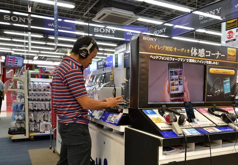 A customer checks out products of Japanese electronics giant Sony, at a shop in Tokyo, on September 18, 2014 (AFP Photo/Yoshikazu Tsuno)