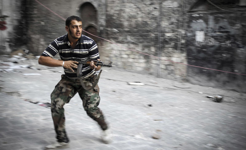 In this Sunday, Nov. 4, 2012 photo, a Free Syrian Army fighter fires his weapon while running for cover in the Bab al-Nasr district of Aleppo, Syria. (AP Photo/Mustafa Karali)