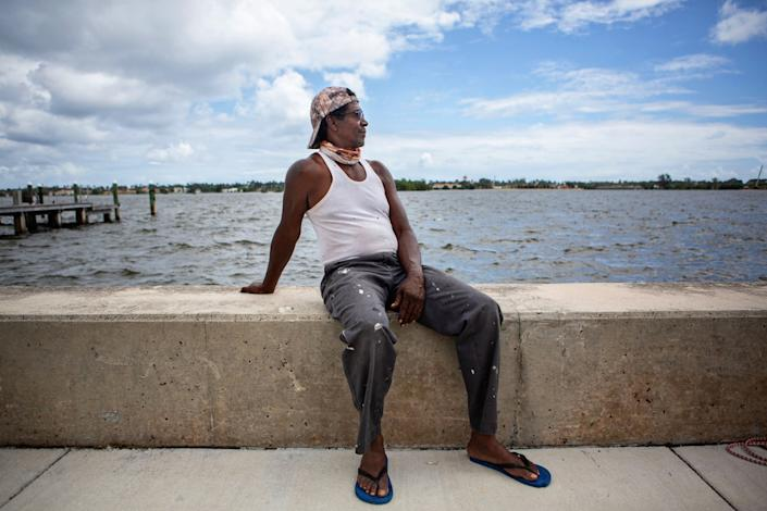 Milton Jackson sits on a low concrete wall next to the waterway along Palm Beach
