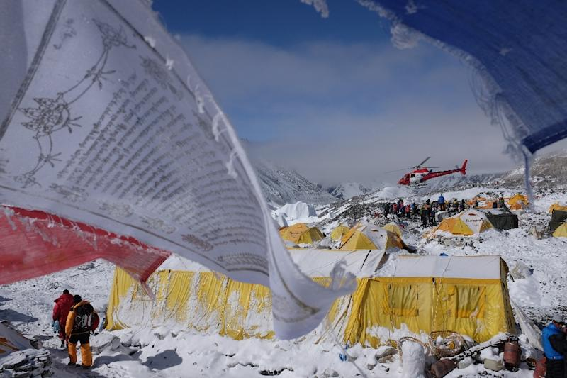 Buddhst prayer flags flutter in the wind near tents as a rescue helicopter takes off from Everest base camp, following a deadly earthquake-triggered avalanche, on April 26, 2015 (AFP Photo/Roberto Schmidt)