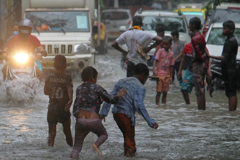 Children play on a flooded street during heavy rains in Mumbai, India on July 16, 2020. Monsoon in India officially lasts from June to September. (Photo by Himanshu Bhatt/NurPhoto via Getty Images)
