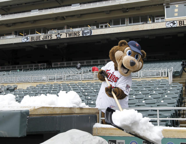Minnesota Twins mascot T.C. shovels snow off the top of the Twins dugout and into the television camera pit before the first baseball game of a doubleheader against the Toronto Blue Jays in Minneapolis, Thursday, April 17, 2014. Wednesday night's game was rescheduled for Thursday night due to a winter storm in Minnesota. (AP Photo/Ann Heisenfelt)