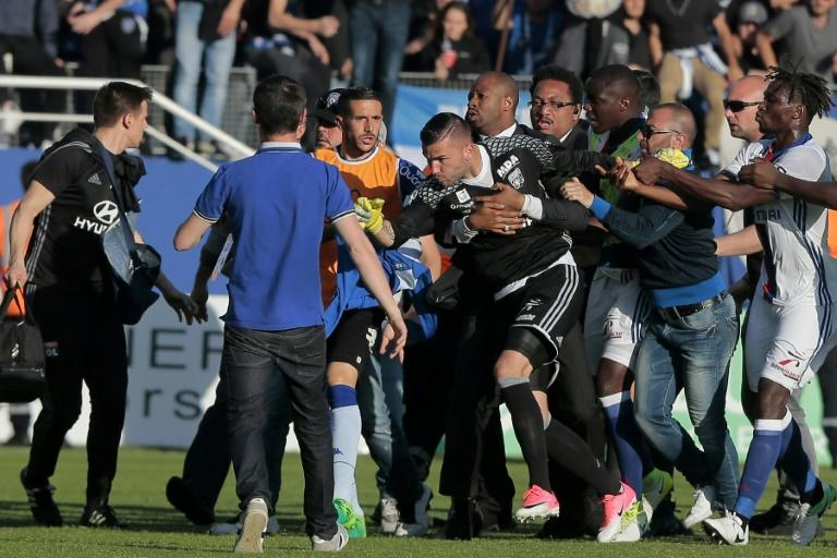 A security staff holds Lyon's goalkeeper Anthony Lopes (C) during scuffles at half-time between some of Lyon's players and Bastia supporters who invaded the pitch, during the French L1 football match Bastia vs Lyon on April 16, 2017