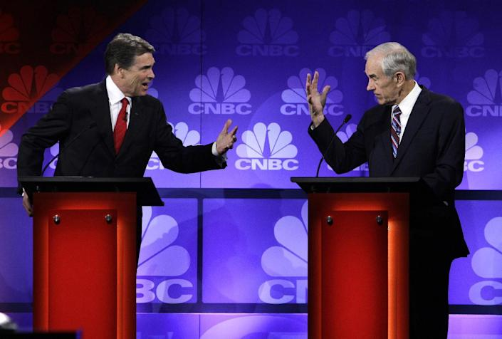 FILE - In this Nov. 9, 2011 file photo, Republican presidential candidates Texas Gov. Rick Perry and Rep. Ron Paul, R-Texas, speak during a Republican Presidential Debate at Oakland University in Auburn Hills, Mich. Perry announced Monday, July 8, 2013, that he would not seek re-election as Texas governor next year. (AP Photo/Paul Sancya, File)