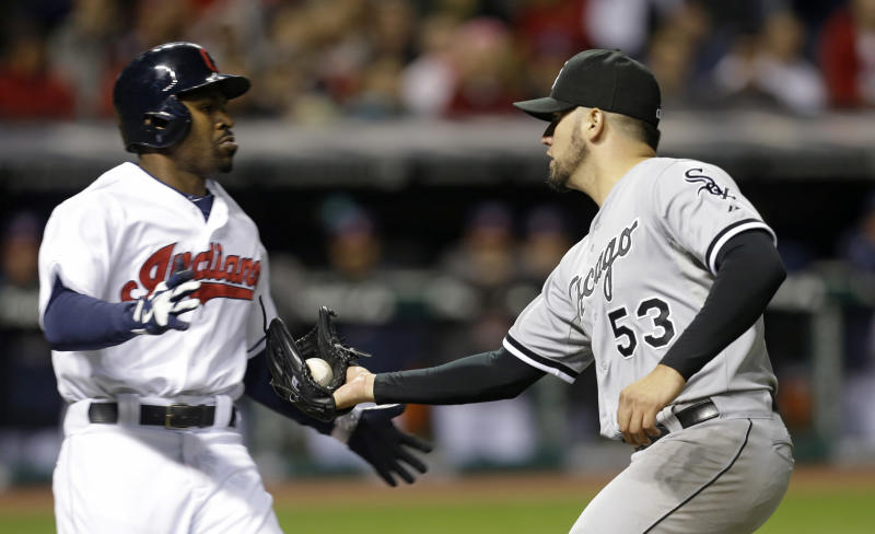 Cleveland Indians' Michael Bourn, left, is tagged out by Chicago White Sox starting pitcher Hector Santiago after Bourn bunted in the seventh inning of a baseball game, Tuesday, Sept. 24, 2013, in Cleveland. (AP Photo/Tony Dejak)