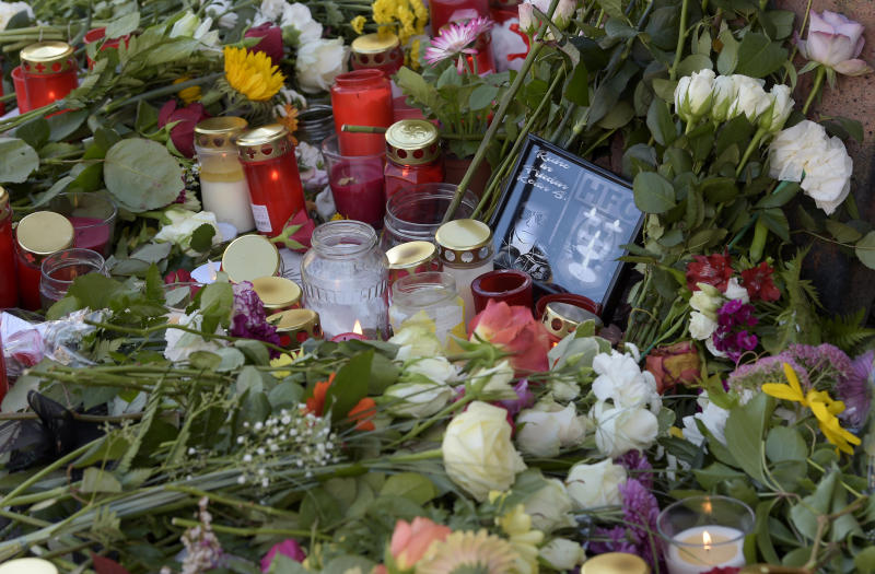 Flowers and candles are placed in front of of a kebab grill in Halle, Germany, Thursday, Oct. 10, 2019. A heavily armed assailant ranting about Jews tried to force his way into a synagogue in Germany on Yom Kippur, Judaism's holiest day, then shot two people to death nearby in an attack Wednesday that was livestreamed on a popular gaming site. (AP Photo/Jens Meyer)