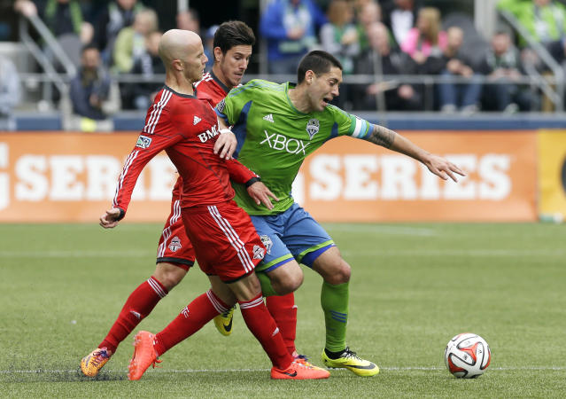 Seattle Sounders' Clint Dempsey, right, battles against Toronto FC's Michael Bradley, left, and Alvaro Rey, center, in the first half of an MLS soccer match on Saturday, March 15, 2014, in Seattle. (AP Photo/Ted S. Warren)