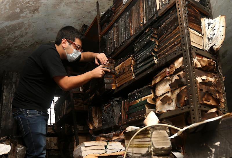 In this picture taken on Sunday, Jan. 5, 2014, a Lebanese activist removes burned books, at the Saeh (Tourist) Library which was set on fire by masked men, in the northern city of Tripoli, Lebanon. Books that were burnt in an arson attack targeting a crammed, chaotic and popular library in the northern Lebanese city of Tripoli have become the latest victim of the country's rising sectarian tensions.(AP Photo/Hussein Malla)