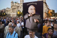 """FILE - In this Friday, Sept. 30, 2016 file photo, a man holds a banner depicting Hungarian Premier Viktor Orban, that reads: """"mini-prime minister"""" during a protest against Orban's policies regarding migrants in Budapest, Hungary. When Hungary and Poland joined the European Union in 2004, after decades of Communist domination, they thirsted for Western democratic standards and prosperity yet, 17 years later, as the EU ramps up efforts to rein in democratic backsliding in both countries, some of the governing right-wing populists in Hungary and Poland are comparing the bloc to their former Soviet oppressors — and flirting with the prospect of exiting the bloc. (AP Photo/Vadim Ghirda, File)"""