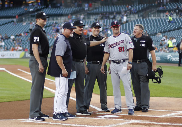 Detroit Tigers manager Ron Gardenhire, second from left, poses with his son Minnesota Twins' Toby Gardenhire (81) and umpires before a baseball game in Detroit, Monday, Sept. 17, 2018. Toby, who managed the Twins Class-A team in Cedar Rapids, is up with the Twins serving and learning under manager Paul Molitor. (AP Photo/Paul Sancya)