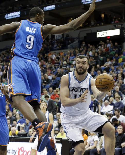Minnesota Timberwolves' Nikola Pekovic, right, of Montenegro, passes the ball under Oklahoma City Thunder's Serge Ibaka, of Congo, in the first quarter of an NBA basketball game, Friday, March 29, 2013, in Minneapolis. (AP Photo/Jim Mone)