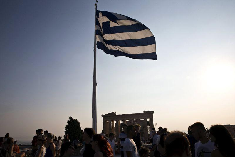 Greek flag flutters in the wind above tourists visiting the archaeological site of the Acropolis hill in Athens, Greece