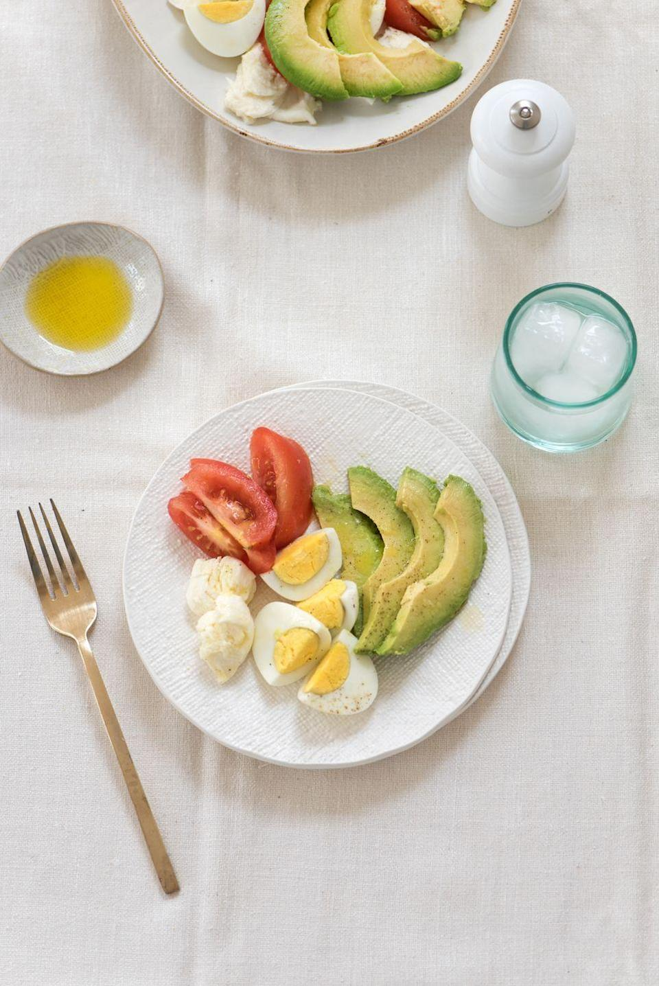 """<p>Kourtney's low-carb lunch includes hard-boiled eggs for protein, as well as avocado, tomato, and fresh mozzarella cheese (though these days, she eats mostly dairy-free). You can snag the recipe on <a href=""""https://poosh.com/kourtney-salad/"""" rel=""""nofollow noopener"""" target=""""_blank"""" data-ylk=""""slk:Poosh"""" class=""""link rapid-noclick-resp"""">Poosh</a>. </p>"""