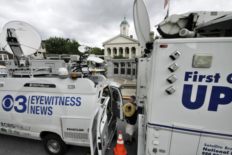 Television satellite trucks set up outside the Centre County Courthouse in Bellefonte, Pa., Monday, June 4, 2012, in preparation for the start of the child sexual abuse trial of former Penn State assistant football coach Jerry Sandusky, on Tuesday. (AP Photo/Gene J. Puskar)
