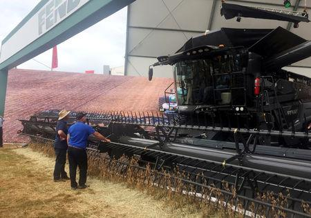 FILE PHOTO: Farmers look at a large grain harvester during the Agrishow farm equipment fair in Ribeirao Preto, Brazil, May 1, 2019. Picture taken May 1, 2019. REUTERS/Marcelo Teixeira/File Photo
